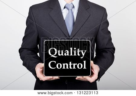 technology, internet and networking in business concept - businessman holding a tablet pc with quality control sign. Internet technologies in business.