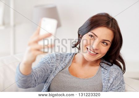 people, technology and leisure concept - happy woman taking selfie with smartphone at home