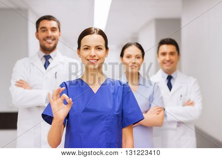 clinic, profession, people, health care and medicine concept - group of happy medics or doctors at hospital corridor showing ok hand sign