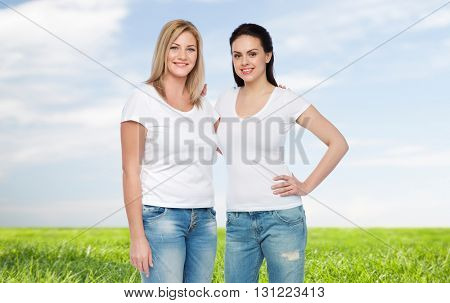 friendship, diverse, body positive and people concept - group of happy different women in white t-shirts hugging over blue sky and grass background