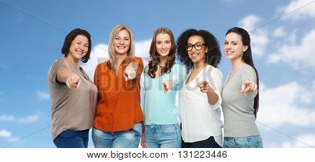 choice, friendship, fashion, diverse people concept - group of happy plus size women in casual clothes pointing finger on you over blue sky and clouds background