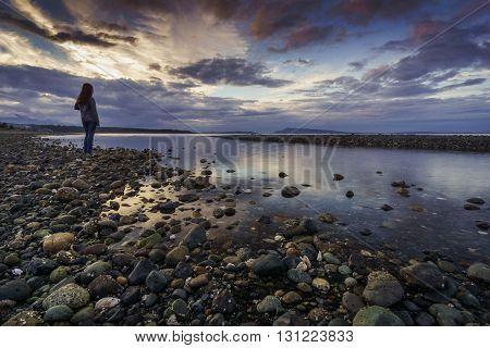 Teen taking in Sunset at Qualicum Beach, British Columbia