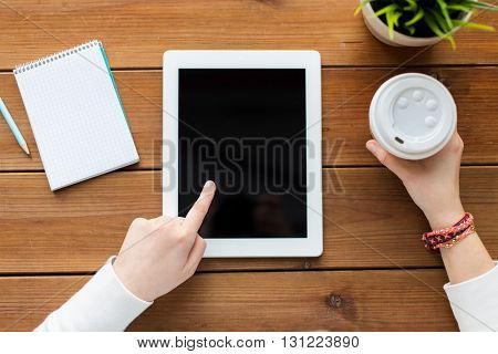 business, education, technology and people concept - close up of woman with blank tablet pc computer screen, notebook and coffee on wooden table