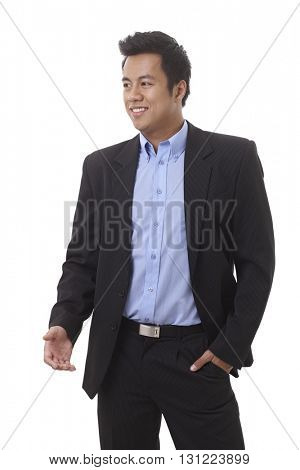 Happy young Asian businessman looking right, gesturing, smiling.