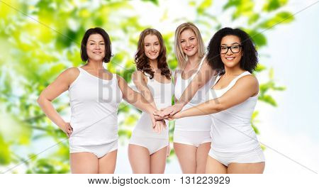 gesture, friendship, beauty, body positive and people concept - group of happy different women in white underwear holding hands together on top over green natural background