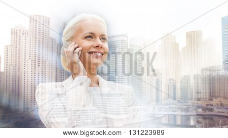 business, technology, communication and people concept - smiling businesswoman with smartphone talking over dubai city background with double exposure effect