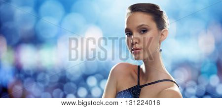 beauty, jewelry, people and luxury concept - beautiful young asian woman with earring over blue lights background