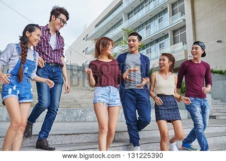 Group of Vietnamese young people walking and chatting outdoors