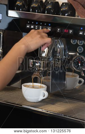 The worker prepares coffee with cream on the coffee machine