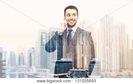 business, technology, communication and people concept - young smiling businessman calling on smartphone over dubai city background with double exposure effect