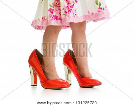 child girl trying mother's shoes on her feet isolated