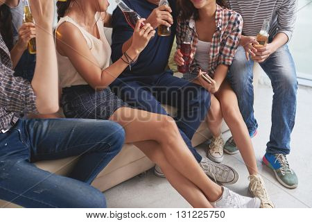 Cropped image of young people drinking beer and chatting
