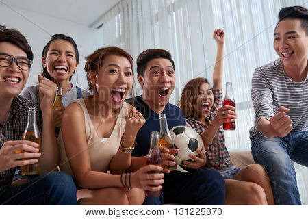 Excited Vietnamese young people watching soccer game at home