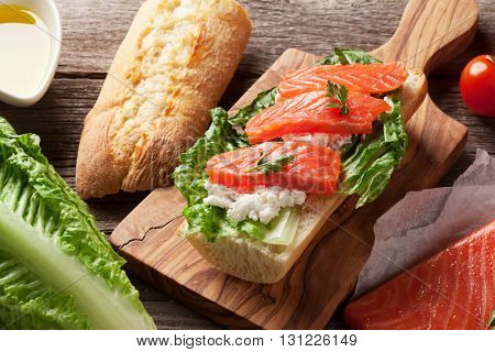 Sandwich with salmon and romaine salad on wooden table