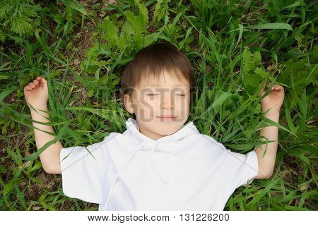 Boy Enjoying Lying Down On The Grass