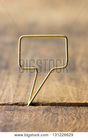 Blank golden speech bubble. Speech bubble made of gold wire on rustic grunge wood. Shallow depth of field.