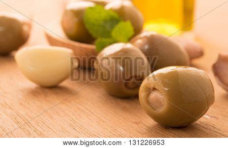 Green olives on a wooden spoon garnished with basil garlic near bowl and olive oil jar