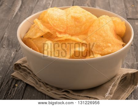 Bowl of potato chips in a black wooden background