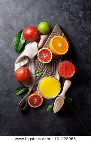 Fresh citruses and juice on dark stone background. Oranges and limes. Top view