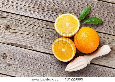 Fresh ripe oranges and juicer on wooden table. Top view with copy space