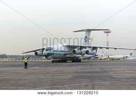MOSCOW, RUSSIA - SEPTEMBER 26, 2014: Cargo airplane IL-76TD Alrosa airlines taxiing to the parking lot with the help of airport Marshal,
