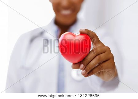 health, medicine and charity concept - close up of african american female doctor hands holding red heart