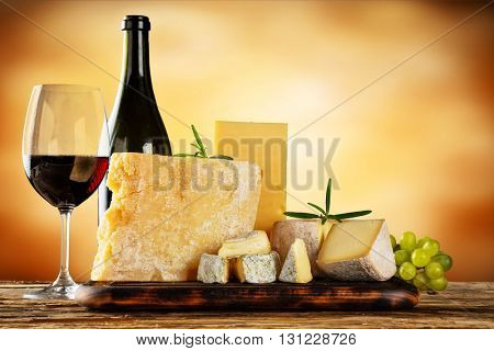 Various types of cheese, glass and bottle of red wine placed on wooden table, copyspace for text. Abstract brown blur background