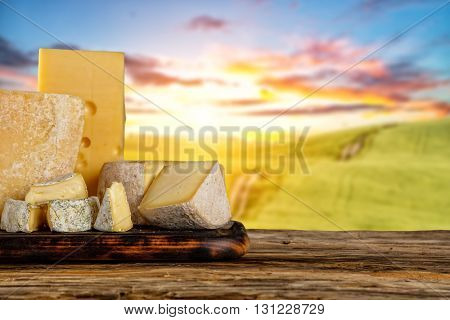 Various types of cheese placed on wooden table, copyspace for text. Beautiful countryside on background