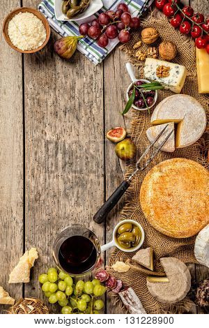 Various kind of traditional cheese and delicacy suitable for wine, placed on wood, shot from high angle view.