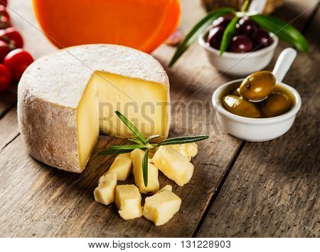 Parmesan cheese on cutting board placed on wood, low depth of focus