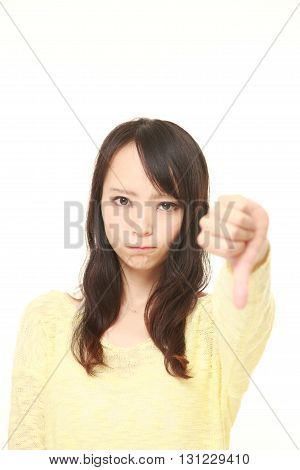 portrait of young Japanese woman with thumbs down gesture on white background