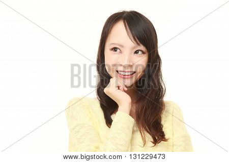 portrait of young Japanese woman dreaming at her future on white background