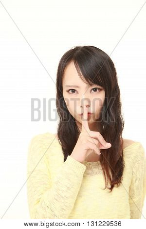 young Japanese woman whith silence gestures on white background