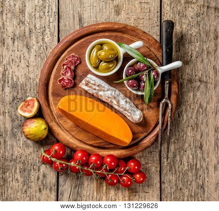 Various kind of traditional cheese and delicacy suitable for wine, placed on wooden cutting board, shot from high angle view.