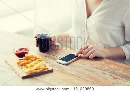 fast food, people, technology and diet concept - close up of woman with smartphone drinking cola and eating french fries, ketchup and deep-fried squid rings at wooden table
