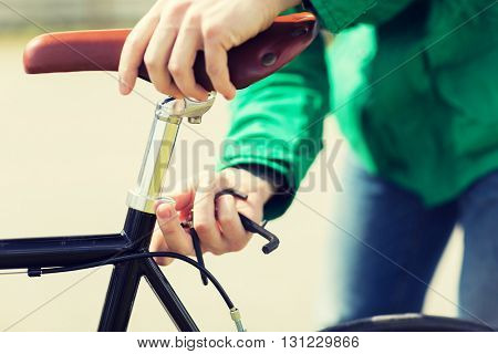 people, vehicle, eisure and lifestyle - close up of man adjusting fixed gear bike saddle high