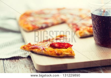 fast food, italian kitchen and eating concept - close up of pizza slice and carbonated drink on wooden table