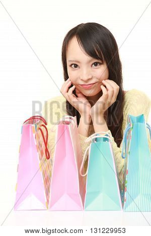 portrait of Japanese woman with shopping bags on white background