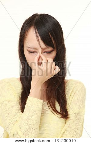 portrait of young Japanese woman suffers from Asthenopia on white background