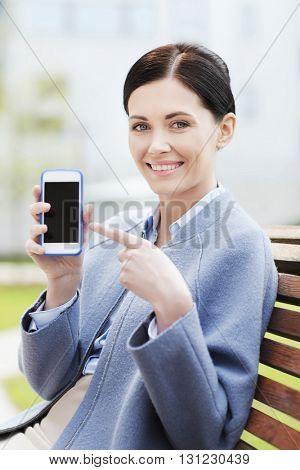 business and people concept - young smiling businesswoman showing smartphone blank screen and sitting on city bench
