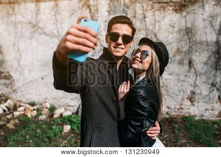 Photo of a young beautiful couple making selfie on wall background
