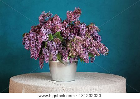 Still life with a bouquet of lilacs in a bucket on a round table with a linen tablecloth with a blue background.