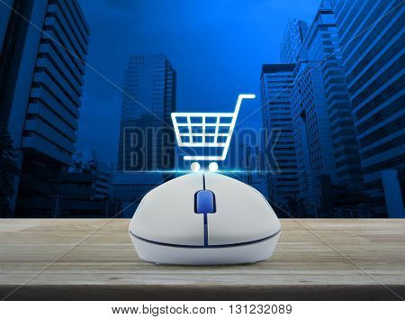Wireless computer mouse with online shopping icon on wooden table in front of city tower background Shopping online concept