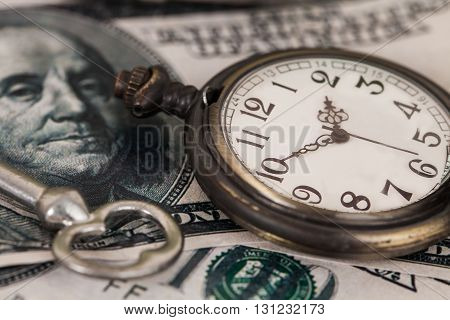 Time and money concept image - old silver pocket watch and US currency .vintage style light and tone