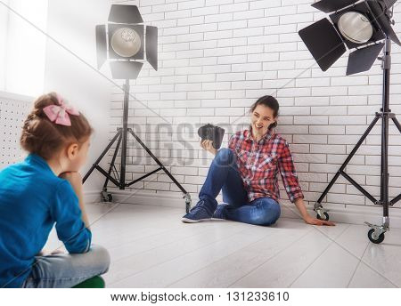 Photographer in motion. Young woman photographs of the child.