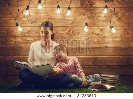 Happy loving family! Pretty young mother reading a book to her daughter