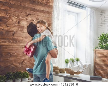 Happy loving family and Father's Day. Father and his daughter. Cute child girl gives a gift to dad.
