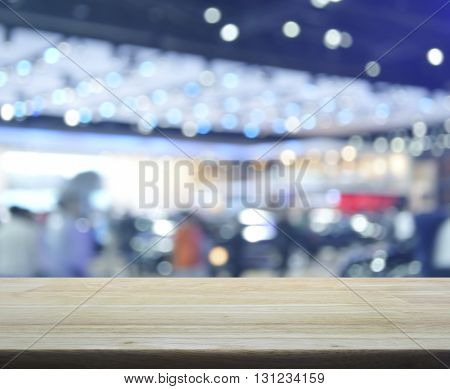 Empty wooden table over defocused light and shadow of shopping mall for product display