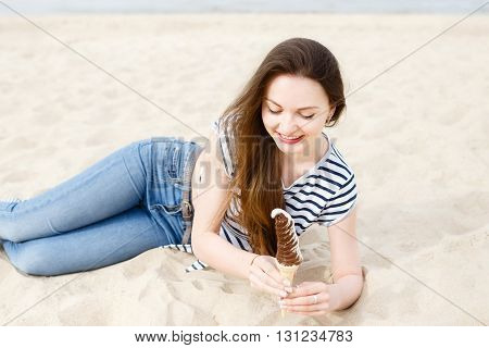 Beautiful stylish girl on the beach against the sea emotionally posing with beautiful make-up and long hair