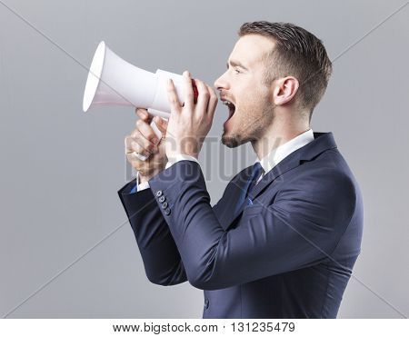 Handsome businessman shouting by megaphone on grey background